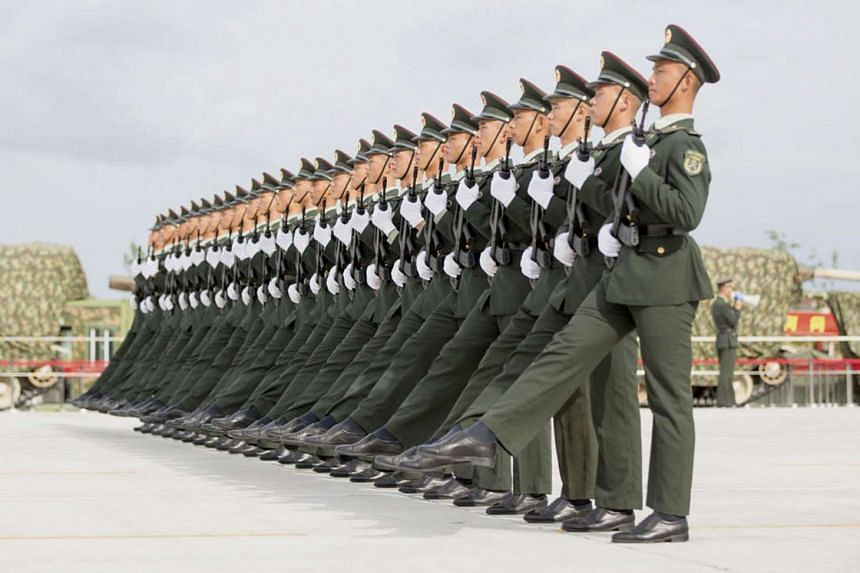 Soldiers of China's People's Liberation Army march with their weapons during a training session for a military parade to mark the 70th anniversary of the end of World War Two, at a military base in Beijing on Sept 1 this year.