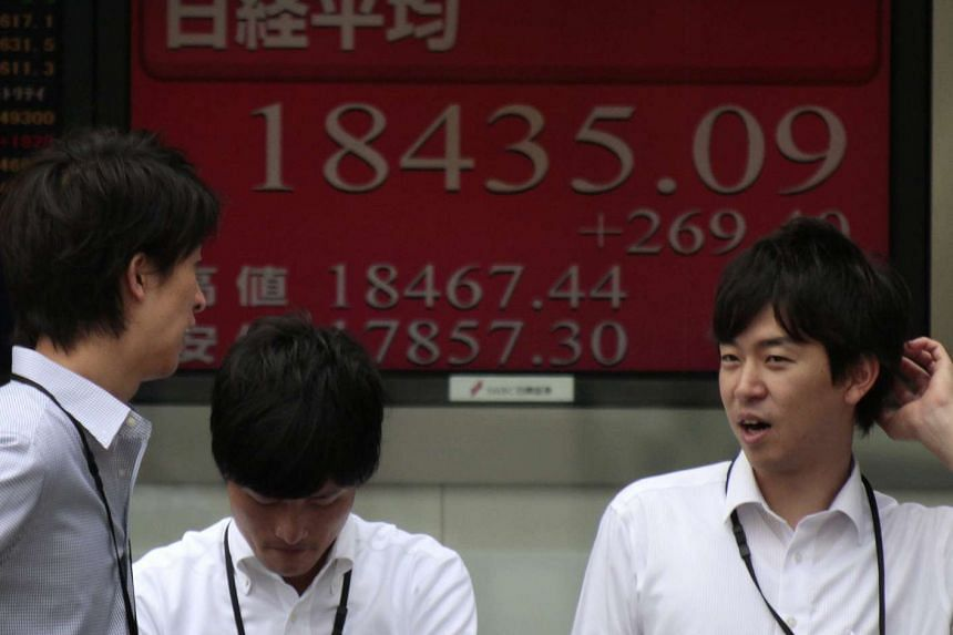Businessmen in front of a display showing Nikkei Stock Average in Tokyo on Sept 2, 2015.