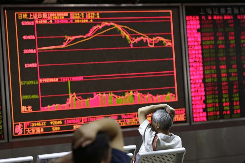 Chinese investors look at an electronic screen showing stock market data at a brokerage house in Beijing, China, on Sept 2 this year.