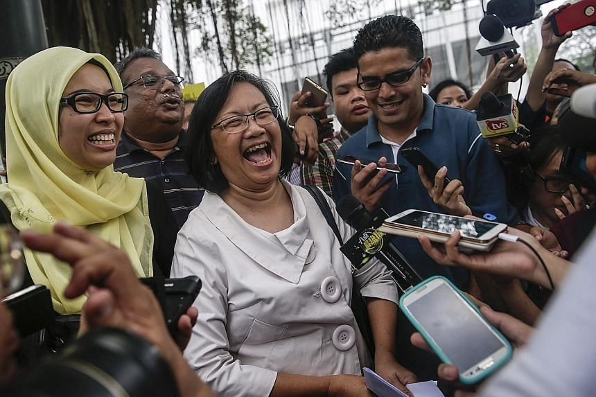 Malaysian police said they want to know where Dr Mahathir Mohamad (left) got his information. Bersih chairman Maria Chin Abdullah (in white) speaking to the media in front of the police headquarters in Kuala Lumpur yesterday. Seven organisers of the