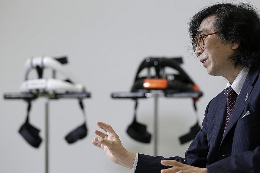 Scientist Yoshiyuki Sankai, pictured with his robot exoskeletons, wants to treat spinal injury patients by using stem cell-related technology to repair nerve connections and robotic suits that aid movement.