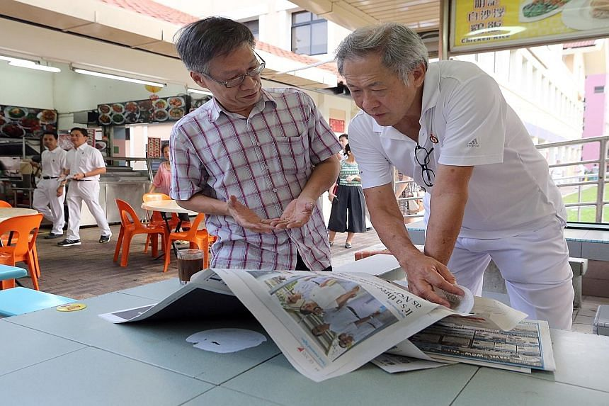 Defence Minister Ng Eng Hen reading the newspapers yesterday at a coffee shop while on a walkabout in Bishan-Toa Payoh GRC. Dr Ng said that while some of the feedback of opposition MPs is important, that of the PAP MPs is critical. He noted that PAP