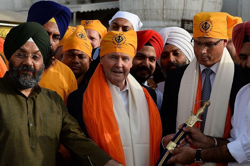 Australian Defence Minister Kevin Andrews (centre) being presented a sword at the Bangla Sahib Gurudwara, or Sikh temple, in New Delhi on Tuesday.
