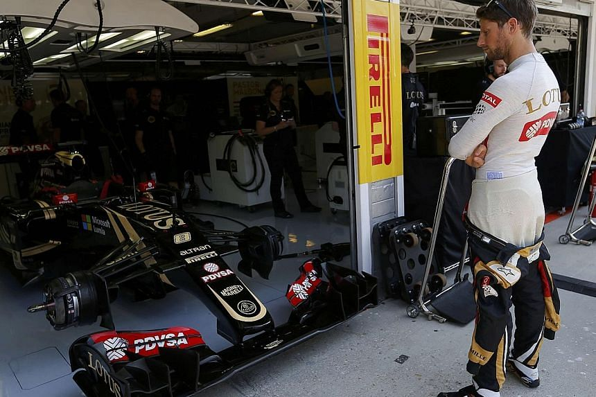 Lotus Formula One driver Romain Grosjean of France in the team garage during the Hungarian Grand Prix weekend. While the team had experienced difficulty in paying for their tyres, Grosjean finished third at the Hungaroring circuit to provide a huge m