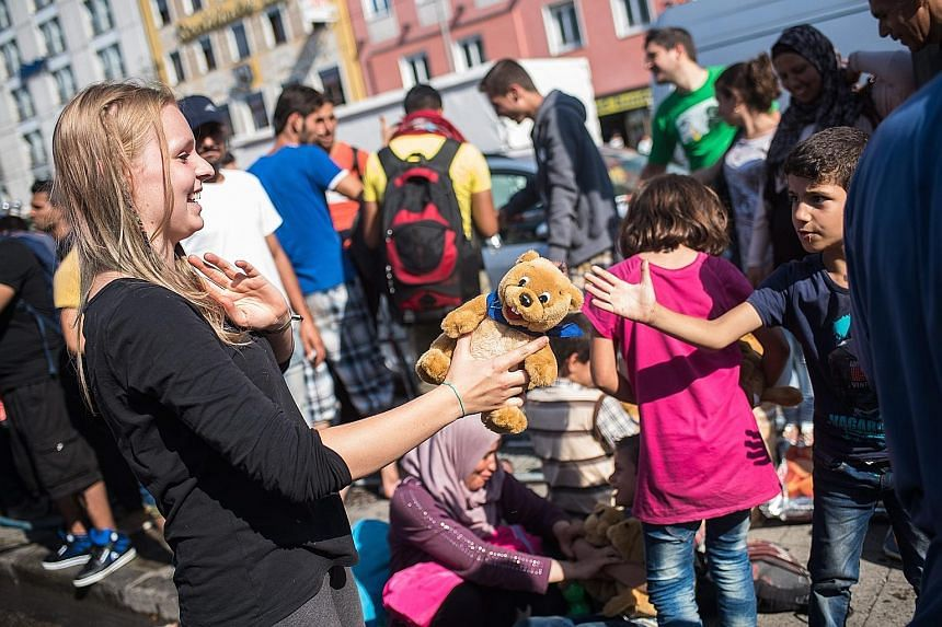 An employee of the Refugee Help Munich initiative handing out soft toys to refugee children at Munich's central train station on Tuesday.
