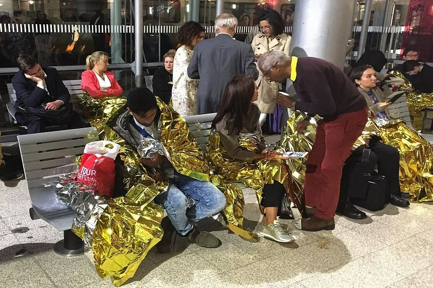 Passengers keeping warm with thermal foil blankets after their Eurostar train was stranded in Calais, France, yesterday. Five train services were suspended for hours, following reports of migrants thronging onboard.