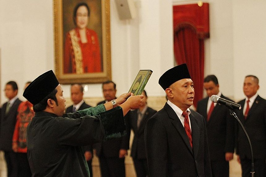 Mr Teten Masduki being sworn in as the Indonesian Chief of Staff at the presidential palace yesterday, taking over from Mr Luhut Pandjaitan who last month took over a key role as the coordinating minister for security and political affairs.