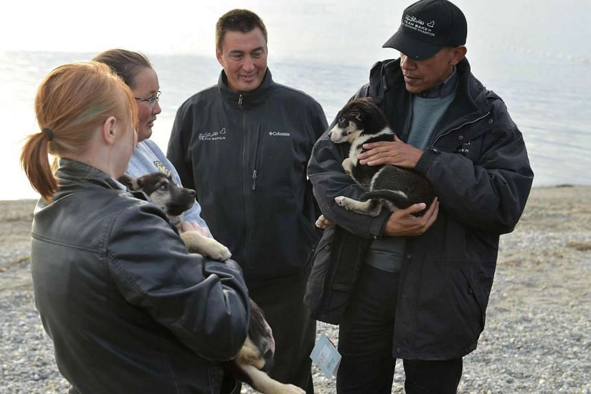 US President Barack Obama holds a puppy belonging to John Baker (2nd R) in Kotzebue, Alaska on Sept 2, 2015. Obama is first US leader to head above the Arctic circle to urge US citizens to take swift action against climate change.