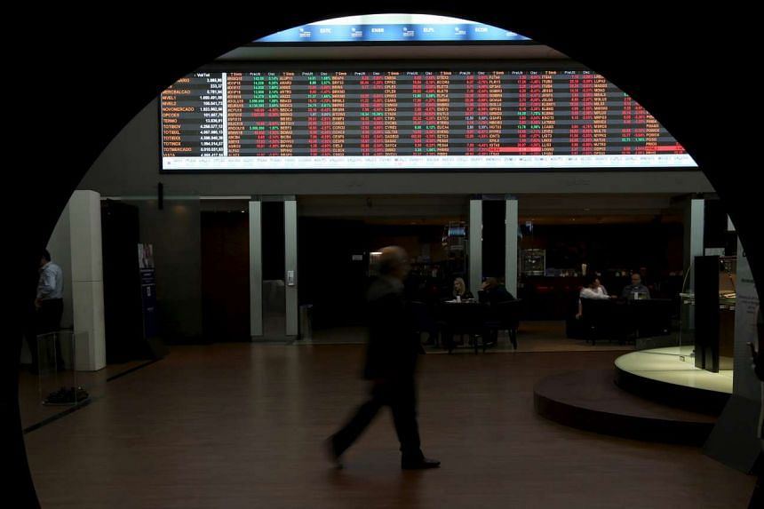 A man walks past the stock quotation board on the floor of Brazil's BM&F Bovespa Stock Market in Sao Paulo.