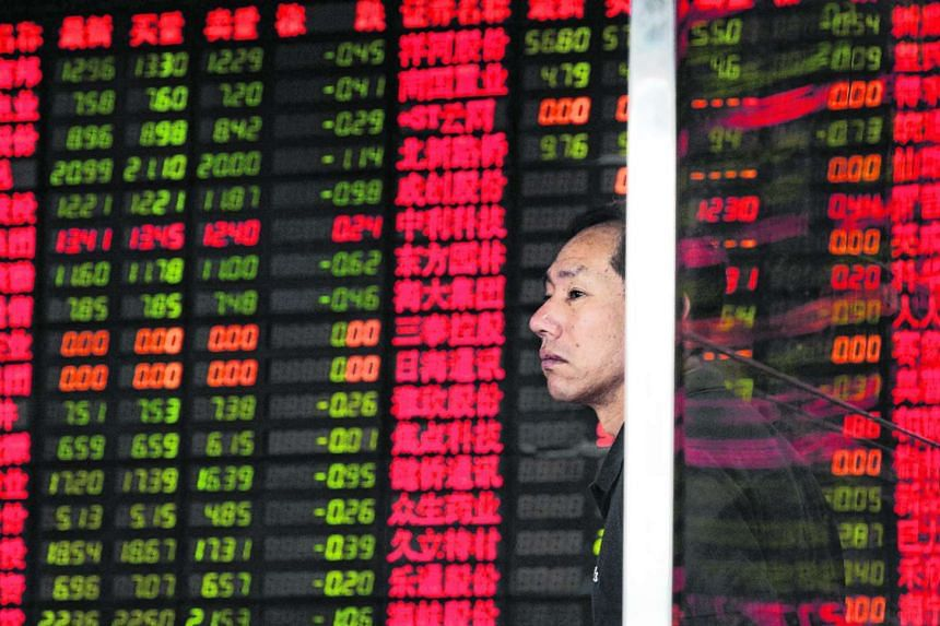 An investor standing in front of an electronic stock board at a brokerage house in Shanghai on Sept 2.