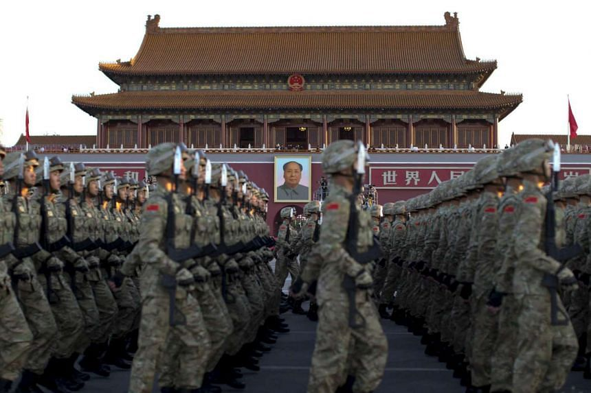 Soldiers of the People's Liberation Army of China march in formation past the Tiananmen Gate and the giant portrait of late chairman Mao Zedong.