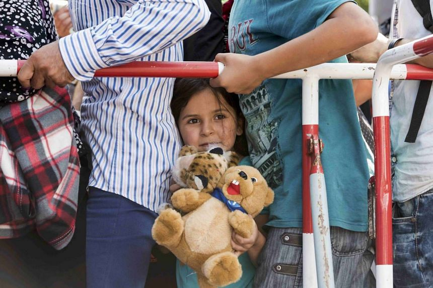 A young migrant girl holds a teddy bear as she stands among other migrants outside the main railway station in Munich, Germany, on Sept 1, 2015.