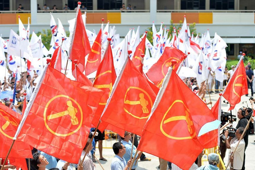 Workers' Party (red flag) and People's Action Party supporters wave flags at Bendemeer Primary School on Nomination Day, Sept 1, 2015.