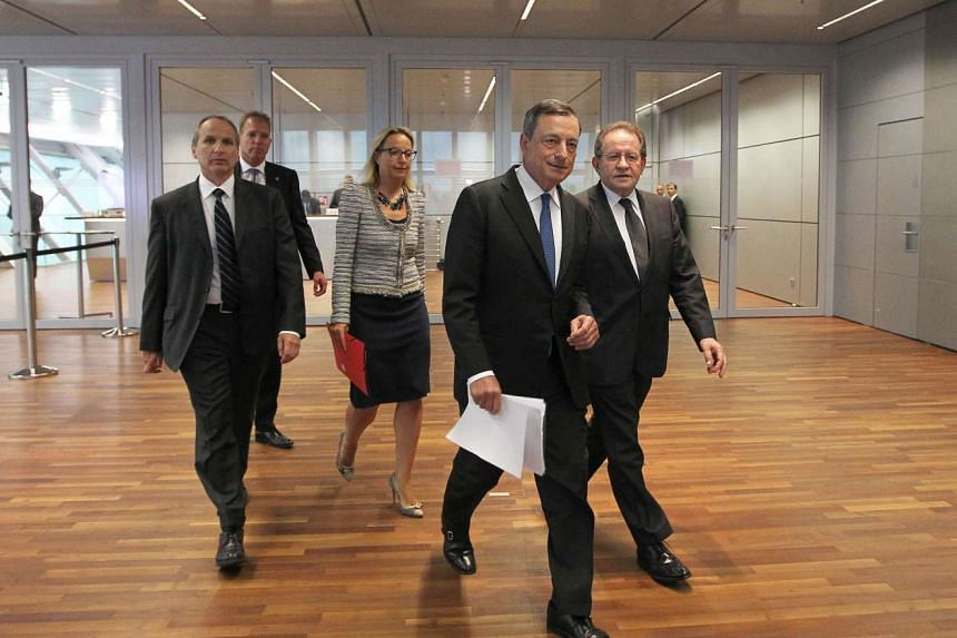 President of the European Central Bank (ECB) Mario Draghi (2ndR) arrives to give the press conference following the meeting of the Governing Council in Frankfurt am Main, western Germany, on September 3, 2015. The ECB holds key refi rate steady at 0.