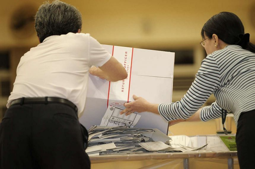 Counting assistants pouring out slips from a ballot box during the 2011 General Election.
