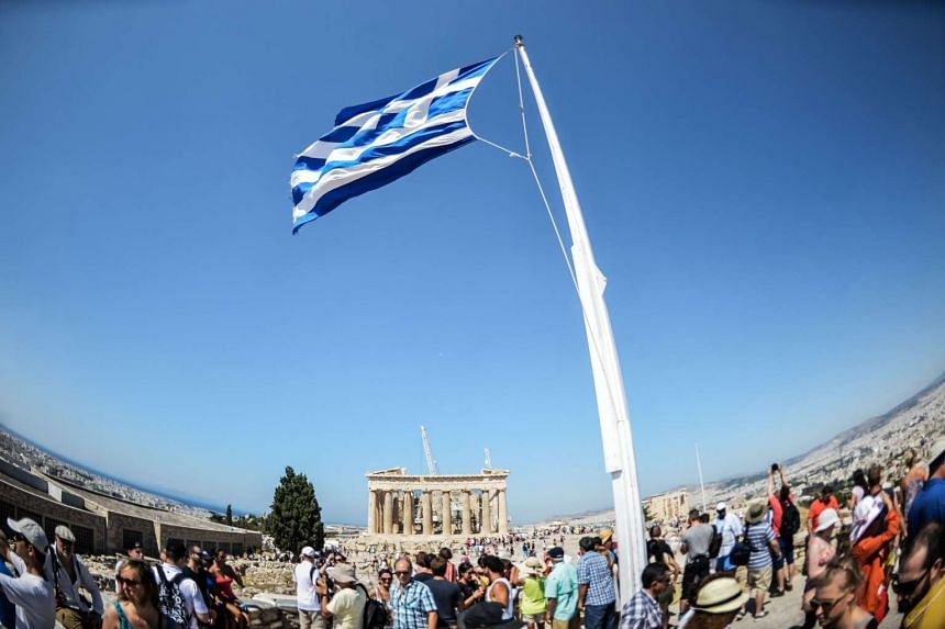 Tourists taking in the view from the Acropolis hill in downtown Athens on July 8, 2015.