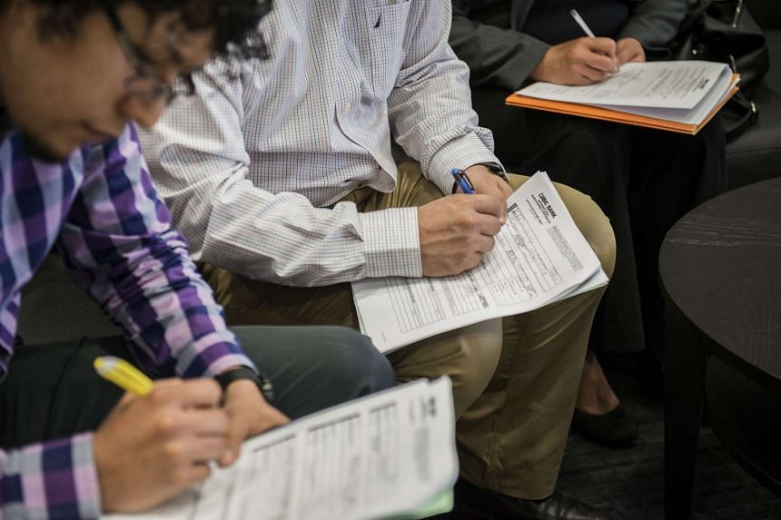 Job seekers fill out applications at the Choice Career Fair in San Antonio, Texas, U.S., on Thursday, April 16, 2015. Fewer than 300,000 American workers filed applications for unemployment benefits for the sixth consecutive week, pointing to labour-