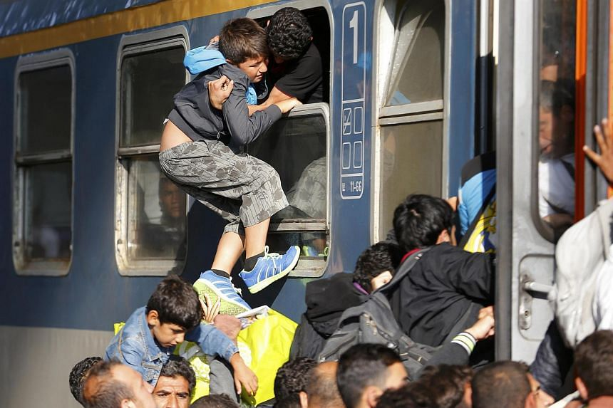 Migrants storm into a train at the Keleti train station in Budapest, Hungary on Sept 3, 2015, as Hungarian police withdrew from the gates after two days of blocking their entry.