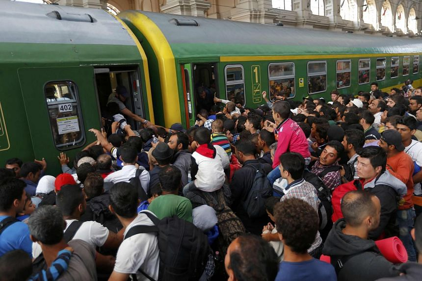 Migrants storm a train at the Keleti train station in Budapest, Hungary, on Sept 3, 2015, as Hungarian police withdrew from the gates after two days of blocking their entry.