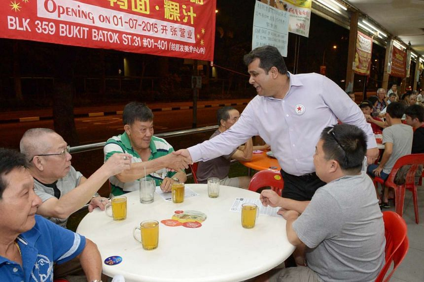Singapore People's Party candidate Ravi Philemon (standing) greeting people during a walkabout in Bukit Batok on Sept 1, 2015.