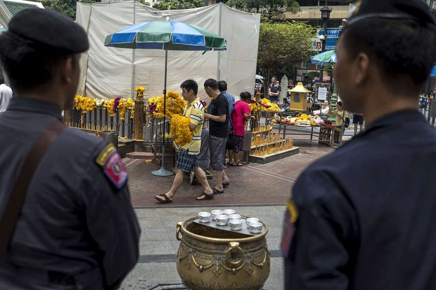 Police officers standing guard as people pray at the Erawan shrine, the site of recent deadly blast, in central Bangkok, Thailand, on Sept 3, 2015.