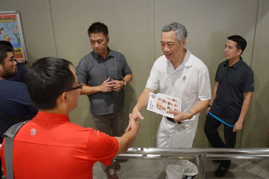 PM Lee shaking hands with a commuter at Ang Mo Kio bus interchange.