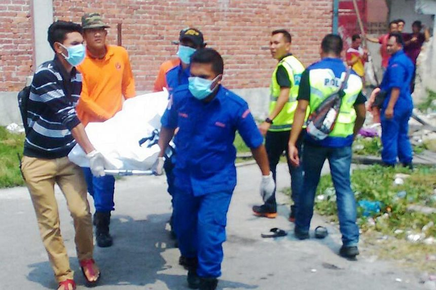 Search teams and police officers carrying the body of a migrant who drowned after their boat capsized off Sabak Bernam in Selangor on Sept 3, 2015.
