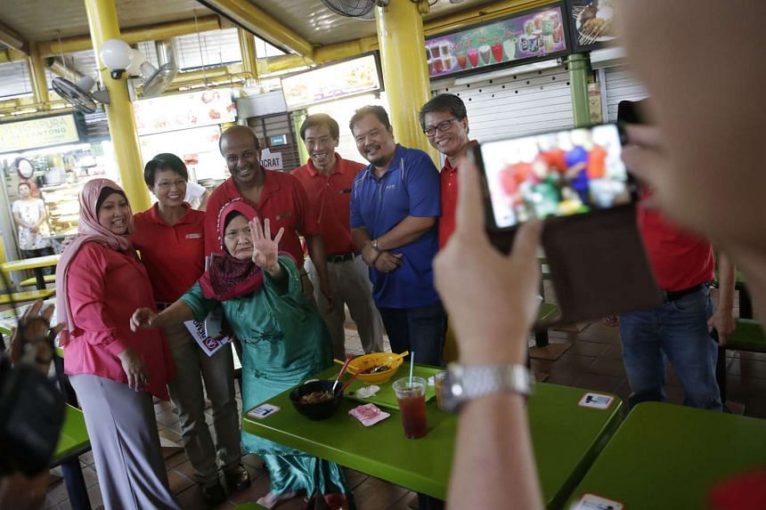 Members of the public taking a photo with red-clad SDP candidates for Holland-Bukit Timah
