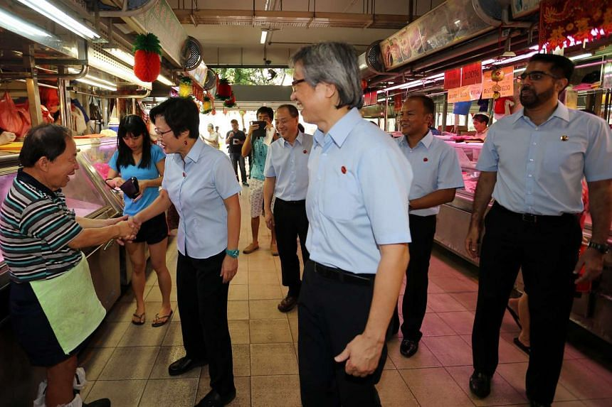 Workers' Party Aljunied GRC candidates (from left) Sylvia Lim, Low Thia Khiang, Chen Show Mao, Muhamad Faisal Abdul Manap and Pritam Singh visiting the market at Hougang Avenue 1 yesterday.