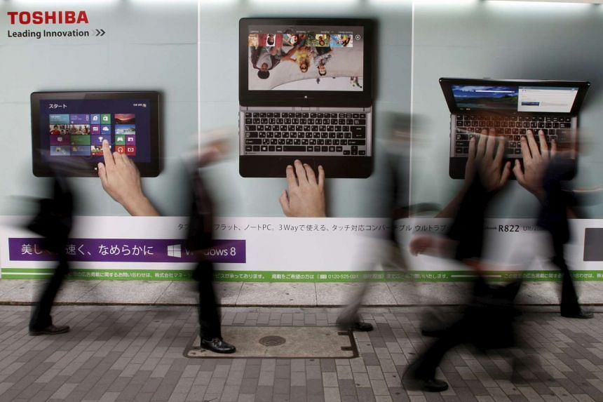 Passers-by walking past an advertisement for Toshiba outside an electronic store in Tokyo.