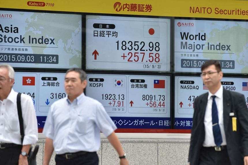 Pedestrians walking past a share price board of the Tokyo Stock Exchange in Tokyo on Sept 3, 2015.