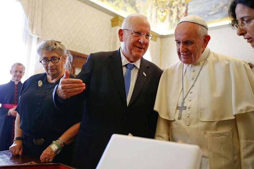 Pope Francis listens to Israel's President Reuven Rivlin as they exchange gifts during a private audience in the Pontiff's private library at the Vatican, Sept 3, 2015