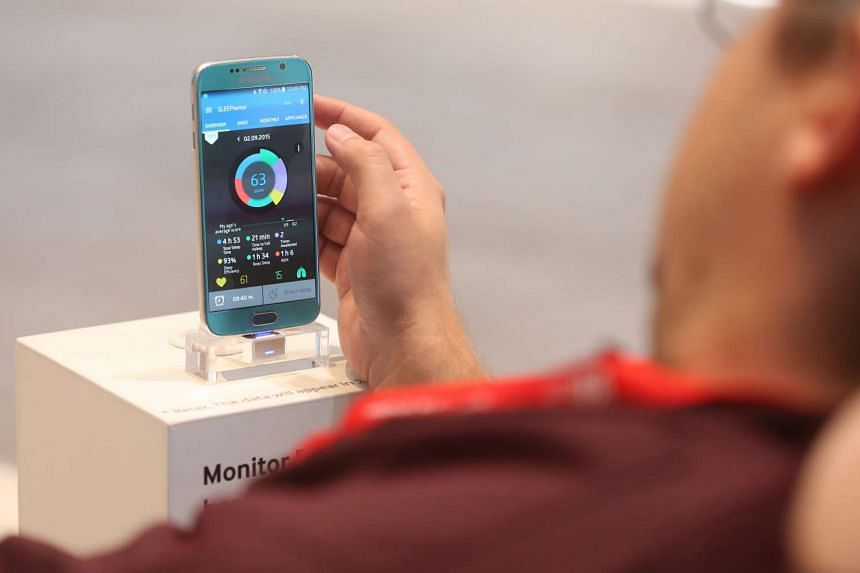 A visitor uses the Samsung Sleep Sense mobile phone app at the Samsung Electronics Co. exhibition stand during previews for the IFA International Consumer Electronics Show in Berlin, Germany, on Sept 3, 2015.