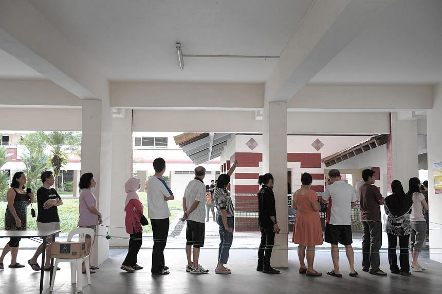 Voters waiting in line for their turn at a polling station at Block 555A Hougang Avenue 51.