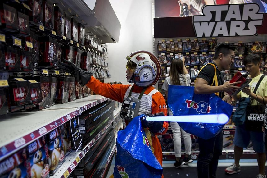 "A fan dressed up as Luke Skywalker picks new toys from the upcoming film ""Star Wars: The Force Awakens"" on ""Force Friday"" after the launch of the film's new toys in Hong Kong, China, on Sept 4, 2015."