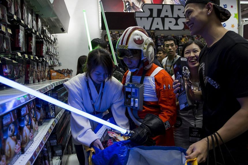 "A fan (centre) dressed as Luke Skywalker picks new toys from the upcoming film ""Star Wars: The Force Awakens"" on ""Force Friday"" after the launch of the film's new toys in Hong Kong, China, on Sept 4, 2015."