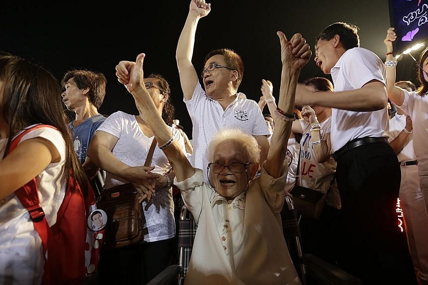 "Above: Bedok resident Quek Jee Yee, 84, cheering along with Transport Minister Lui Tuck Yew (right) at the People's Action Party rally at Bedok Stadium yesterday. Right: A Workers' Party supporter holding up a ""hammer"", the symbol of the opposition p"