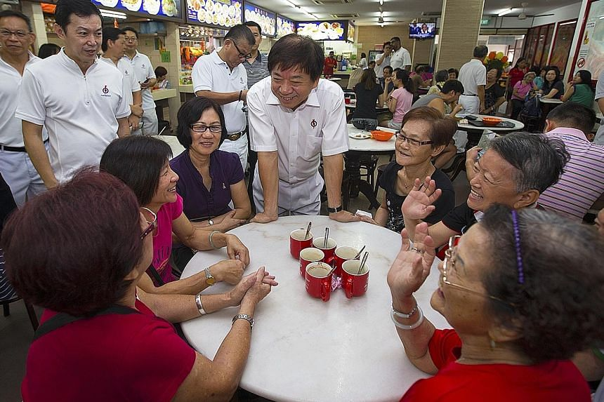 Mr Khaw Boon Wan speaking to diners at an eatery during his walkabout in Woodlands yesterday.