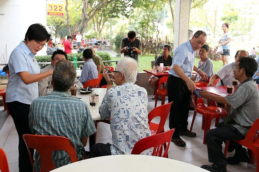 Workers' Party chief Low Thia Khiang and chairman Sylvia Lim (both standing) reaching out to voters at a coffee shop during one of their walkabouts.