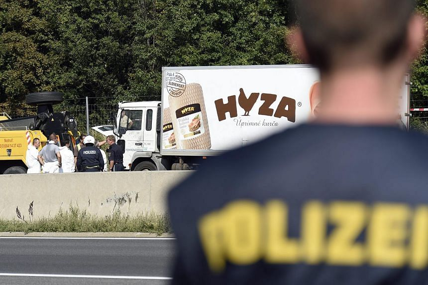 Forensic experts investigate a truck in which refugees were found dead as it stands on freeway autobahn A4 between Parndorf and Neusiedl, Austria on Aug 27, 2015.