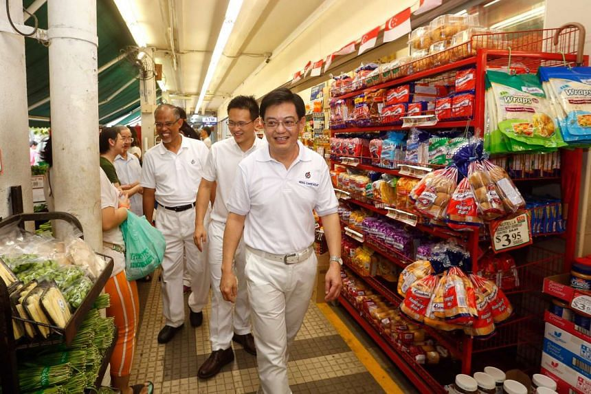 Minister Heng Swee Keat (centre) leading his PAP Tampines candidates walkabout at Tampines on Sept 4, 2015. Behind him are Desmond Choo and Masagos Zulkifli.