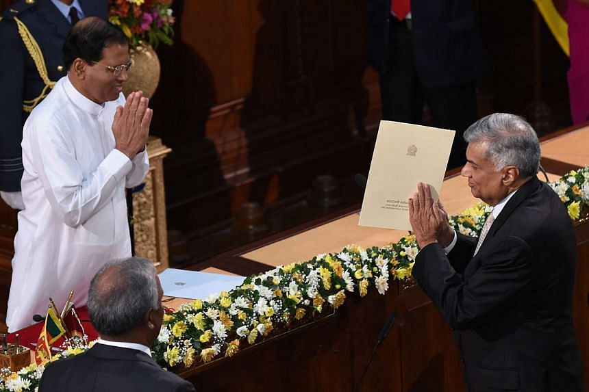 Sri Lanka's Prime Minister Ranil Wickremesinghe (right) after taking an oath as he is sworn in as minister of policy planning and economic affairs in front of Sri Lanka's President Maithripala Sirisena in Colombo on Sept 4, 2015.