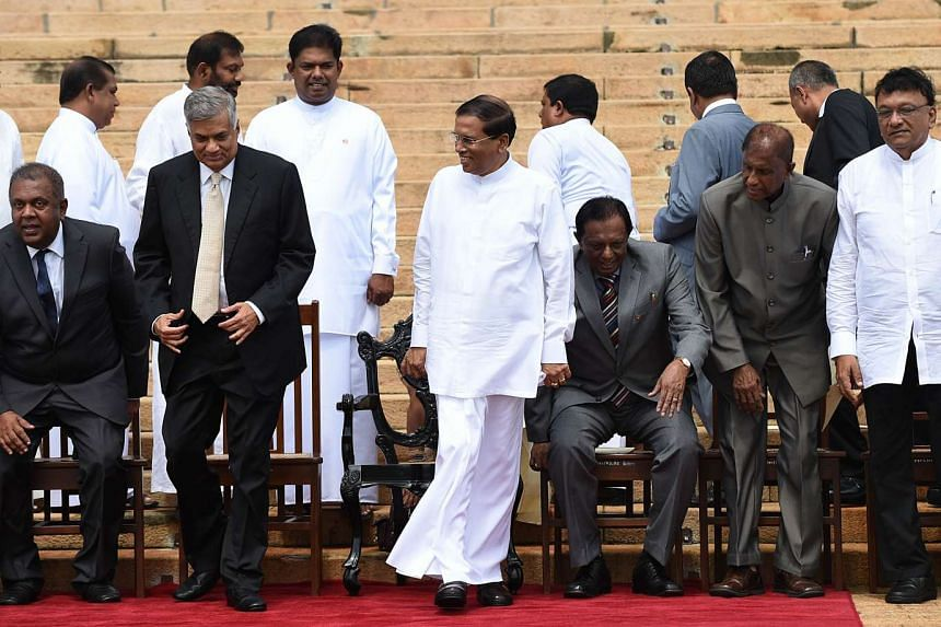 Sri Lanka's President Maithripala Sirisena (centre) shares a moment with Prime Minister Ranil Wickremesinghe (second from left) next to Foreign Minister Mangala Samaraweera (left) after they pose for group photos at the swearing-in ceremony for newly