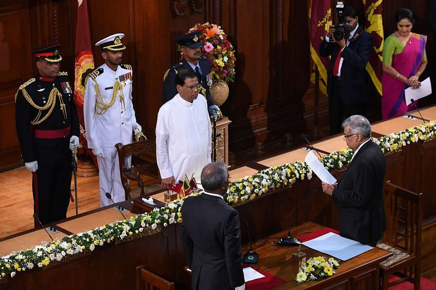 Sri Lanka's Prime Minister Ranil Wickremesinghe (right) reads from a sheet while taking an oath as he is sworn in as minister of policy planning and economic affairs in front of Sri Lanka's President Maithripala Sirisena (centre) in Colombo on Sept 4