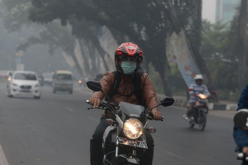 A motorcyclist wearing a mask as he navigates the roads under challenging conditions in Palembang, Sumatra, on Aug 27, 2015.