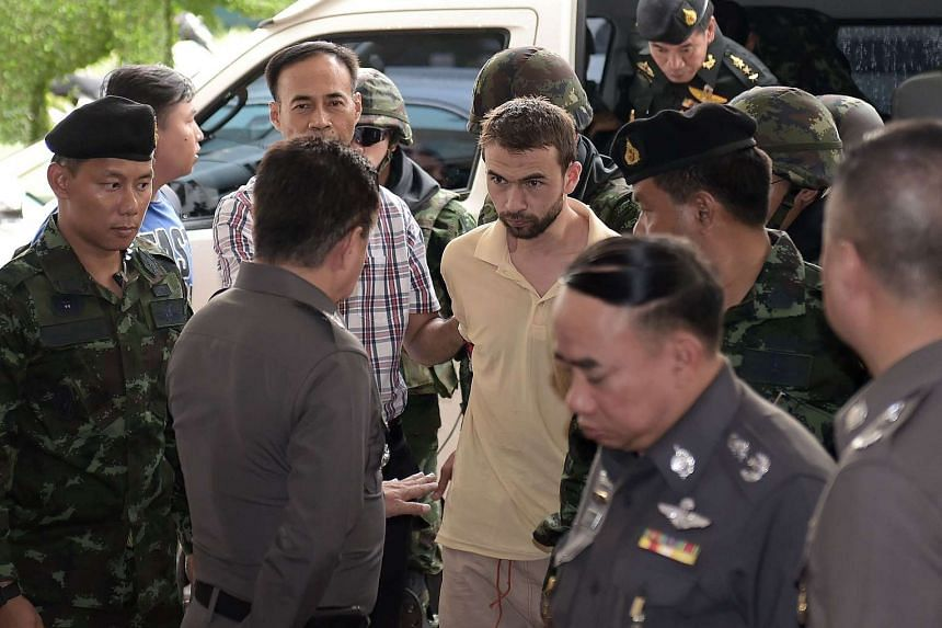 Adem Karadag (centre), is escorted by soldiers as he arrives to be questioned by police officers at Bangkok's Metropolitan Police Station on Sept 4, 2015.