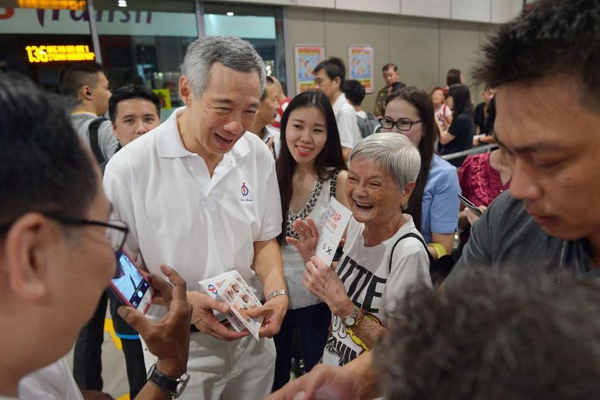 PM Lee surrounded by excited commuters at Ang Mo Kio bus interchange, where he handed out fliers, posed for pictures with fans and signed autographs.