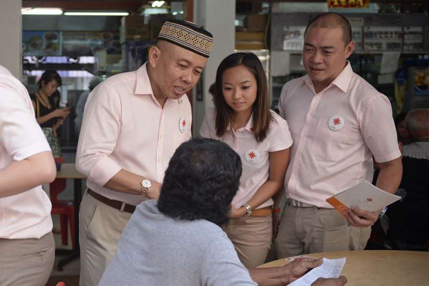 NSP candidates Yadzeth Hairis, Kevryn Lim and Eugene Yeo talking to a resident in Woodlands.