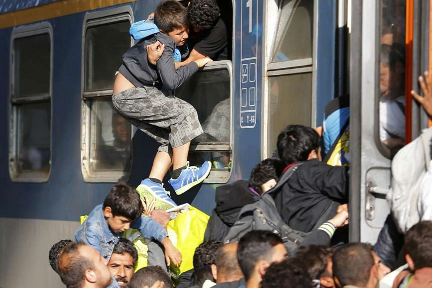 Migrants storming onto a train at the Keleti train station in Budapest, Hungary, yesterday after the station was reopened.