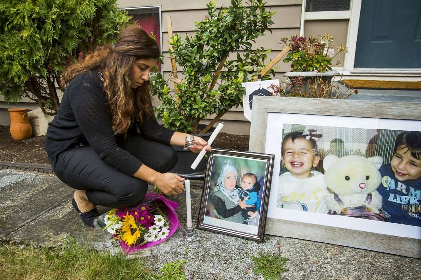 A woman lighting a candle near photographs of the boys outside, the sister of Syrian refugee Abdullah Kurdi, Tima's home in Coquitlam, British Columbia on Sept 3, 2015.